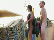Attractive naked people on the street side nude beach tease each other